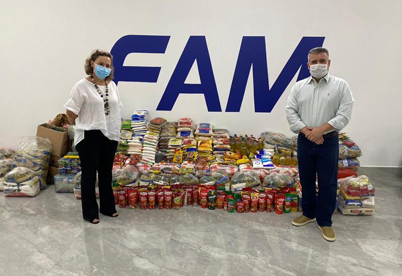 Lionela e Gustavo com alimentos arrecadados na campanha (Foto: FAM | Divulgação)